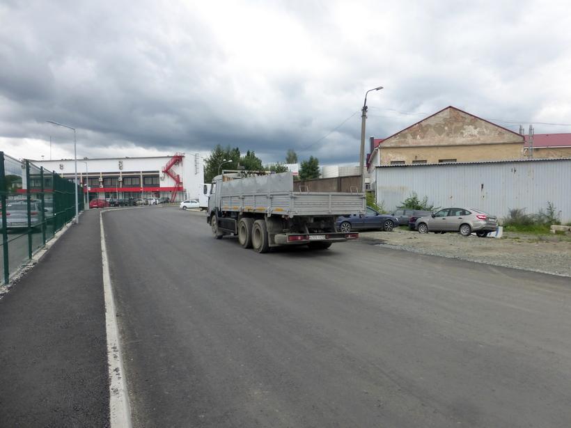 Автомобиль с надпись «Экорус» выезжает с территории ООО «Киберсталь». В кузове ничего не видно.